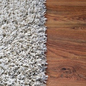 Two part split image of white shaggy carpet and brown wooden floor